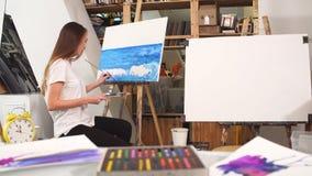 Retrato de un artista agradable con una paleta en manos en el estudio del arte almacen de metraje de vídeo