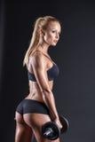 Retrato de un atleta hermoso de la muchacha con una pesa de gimnasia en estudio fotografía de archivo libre de regalías