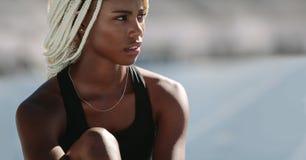 Retrato de un atleta de sexo femenino que se sienta en pista corriente fotos de archivo