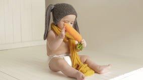 Retrato de un bebé en un traje del conejito Risas y juegos del niño pequeño con el juguete almacen de metraje de vídeo