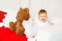 Retrato de un bebé hermoso con un oso de peluche marrón suave i Foto de archivo