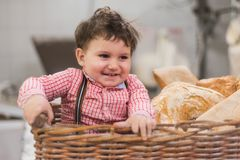 Retrato de un bebé lindo dentro de una cesta con pan en la panadería foto de archivo