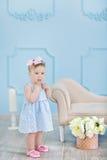 Retrato de un bebé lindo en un fondo ligero con una guirnalda de flores en su cabeza que se sienta en cesta del sofá Imagen de archivo libre de regalías