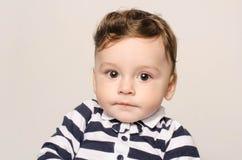 Retrato de un bebé lindo que mira la cámara con sus ojos grandes Imágenes de archivo libres de regalías
