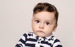 Retrato de un bebé lindo que mira la cámara con sus ojos grandes Fotos de archivo libres de regalías