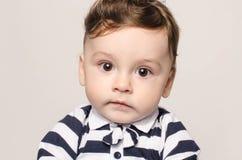 Retrato de un bebé lindo que mira la cámara con sus ojos grandes Fotos de archivo