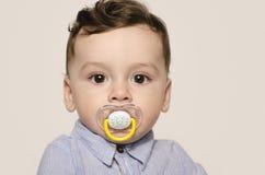 Retrato de un bebé lindo que mira la cámara con un pacificador en su boca Fotografía de archivo