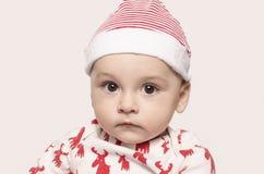 Retrato de un bebé lindo que mira la cámara que lleva un sombrero de Papá Noel Imagen de archivo libre de regalías
