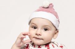 Retrato de un bebé lindo que mira la cámara que lleva un sombrero de Papá Noel Foto de archivo