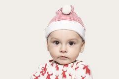 Retrato de un bebé lindo que mira la cámara que lleva un sombrero de Papá Noel Fotografía de archivo