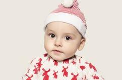 Retrato de un bebé lindo que mira la cámara que lleva un sombrero de Papá Noel Imágenes de archivo libres de regalías