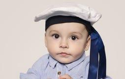 Retrato de un bebé lindo que mira la cámara que lleva un sombrero del marinero Imagen de archivo