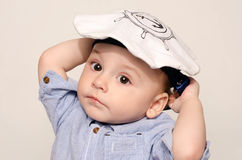 Retrato de un bebé lindo que mira la cámara que lleva un sombrero del marinero Fotos de archivo