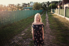 Retrato de un bebé que hace girar en un campo en luz de la puesta del sol Fotos de archivo libres de regalías