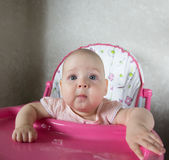 Retrato de un bebé que se sienta en un highchair Fotos de archivo