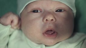 Retrato de un bebé recién nacido en el traje verde apacible con un pacificador amarillo metrajes