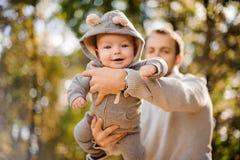 Retrato de un bebé sonriente lindo en manos del padre imagen de archivo