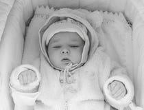 Retrato de un bebé tres-mes-viejo soñoliento que miente en una cuna en ropa rosada, visión superior blanco y negro foto de archivo libre de regalías