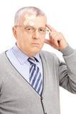 Retrato de un caballero maduro con el dolor de cabeza que mira la cámara Foto de archivo libre de regalías