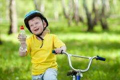 Retrato de un cabrito lindo en la bicicleta Foto de archivo libre de regalías