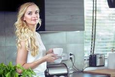 Retrato de un café de consumición adorable de la mujer joven Imagen de archivo libre de regalías