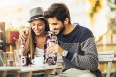 Retrato de un café de consumición de los pares atractivos alegres Imagen de archivo