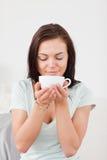 Retrato de un café de consumición de la mujer dark-haired Imagenes de archivo