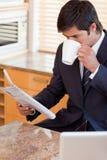 Retrato de un café de consumición del hombre de negocios mientras que lee las noticias Foto de archivo libre de regalías