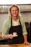 Retrato de un camarero que sostiene una taza de café Imagenes de archivo