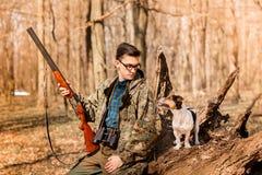 Retrato de un cazador de yang con un perro en el bosque foto de archivo