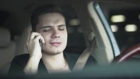 Retrato de un chicle y de hablar del hombre joven en un teléfono móvil en el primer del coche almacen de metraje de vídeo
