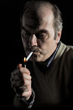 Retrato de un cigarrillo de la iluminación del hombre imagen de archivo libre de regalías
