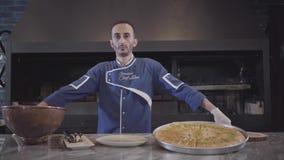 Retrato de un cocinero acertado confiado en una situación uniforme azul al lado de un plato delicioso, apetitoso en la cocina almacen de metraje de vídeo