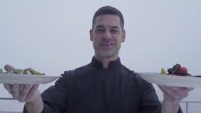 Retrato de un cocinero barbudo sonriente en los platos deliciosos de las placas uniformes negras del demostriruet dos que se colo almacen de metraje de vídeo
