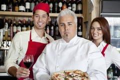 Retrato de un cocinero confiado que sostiene la pizza con el personal de la espera en fondo foto de archivo