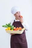 Retrato de un cocinero que sostiene la fruta y verdura Fotos de archivo