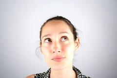 Retrato de un cogitate hermoso de la mujer aislado en un backg blanco imagen de archivo