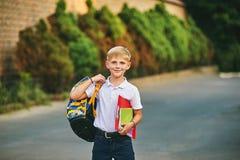 Retrato de un colegial en la calle con una mochila y los cuadernos Imagen de archivo