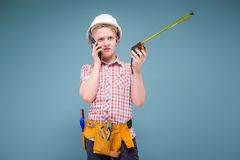 Retrato de un constructor joven en un casco y de una cinta métrica en su mano Imagen de archivo libre de regalías