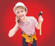 Retrato de un constructor joven en un casco y de una cinta métrica en su mano Foto de archivo