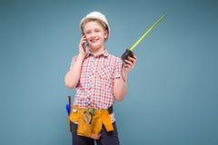 Retrato de un constructor joven en un casco y de una cinta métrica en su mano Fotos de archivo libres de regalías