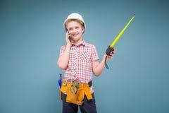 Retrato de un constructor joven en un casco y de una cinta métrica en su mano Fotografía de archivo libre de regalías