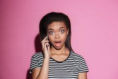 Retrato de un cotilleo afroamericano de la mujer en el teléfono móvil Imagen de archivo libre de regalías