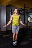 Retrato de un deportista joven en el sportwear que salta con una cuerda de salto contra la pared de ladrillo en el gimnasio Fotografía de archivo libre de regalías
