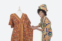 Retrato de un diseñador de moda de sexo femenino afroamericano que trabaja en dashiki sobre fondo gris fotografía de archivo
