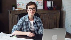 Retrato de un diseñador gráfico de sexo femenino joven que se sienta en la tabla con la tableta de gráficos metrajes