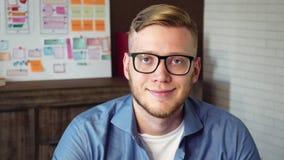 Retrato de un diseñador gráfico de sexo masculino joven que se sienta en la tabla con la tableta de gráficos almacen de metraje de vídeo