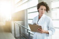 Retrato de un doctor de sexo femenino serio que lleva a cabo su carta paciente en hospital moderno brillante foto de archivo