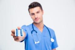 Retrato de un doctor de sexo masculino que sostiene píldoras Fotos de archivo libres de regalías