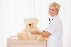 Retrato de un doctor rubio con el oso del estetoscopio y de peluche Foto de archivo libre de regalías